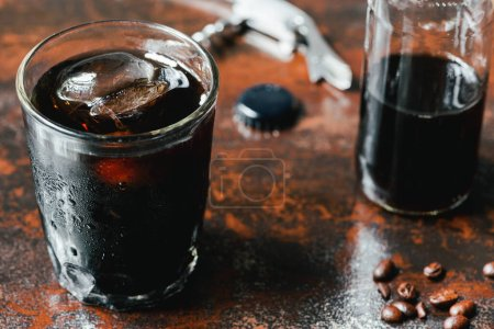 Photo for Selective focus of cold brew coffee with ice in glass and bottle near coffee beans on rusty surface - Royalty Free Image