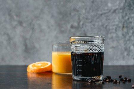 foyer sélectif de café infusé à froid dans le verre près du jus d'orange et des grains de café