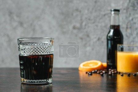enfoque selectivo de café de cerveza fría cerca de botella, jugo de naranja y granos de café