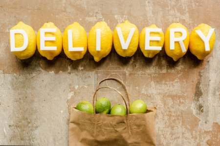 Photo for Top view of word delivery on lemons near paper bag with limes on weathered surface - Royalty Free Image