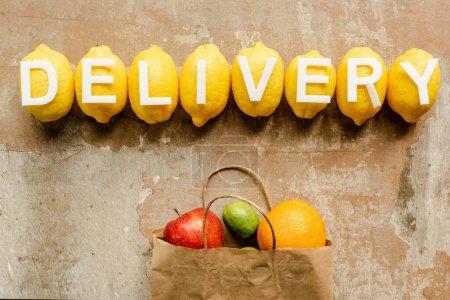 Photo pour Vue du dessus de la livraison de mot sur des citrons près du sac en papier avec des fruits sur la surface altérée - image libre de droit