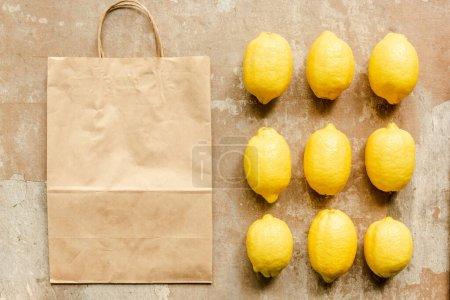 Photo pour Pose plate avec des citrons près du sac en papier sur la surface altérée - image libre de droit
