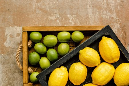 top view of lemons and limes in wooden boxes on weathered surface