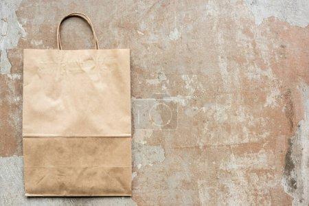 Photo pour Vue du dessus du sac en papier beige sur la surface altérée - image libre de droit
