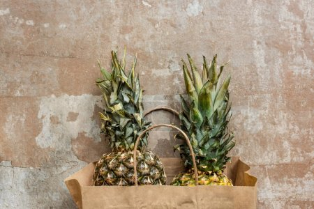 Photo pour Vue du dessus des ananas mûrs dans un sac en papier sur une surface altérée - image libre de droit