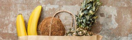 Photo pour Vue du dessus des fruits frais tropicaux dans un sac en papier sur une surface altérée, culture panoramique - image libre de droit