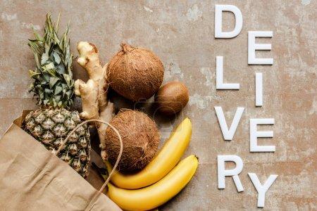 Photo pour Vue du dessus des fruits frais tropicaux et de la racine de gingembre dans un sac en papier sur une surface altérée avec livraison de mots - image libre de droit