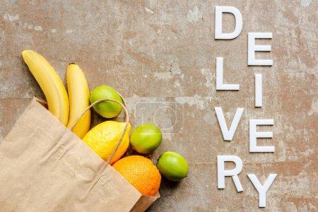 Photo pour Vue du dessus de la livraison de mot près du sac en papier avec des fruits frais sur la surface altérée - image libre de droit