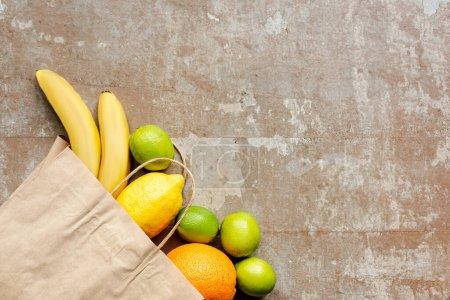 Photo pour Vue du dessus du sac en papier avec des fruits frais sur la surface altérée - image libre de droit