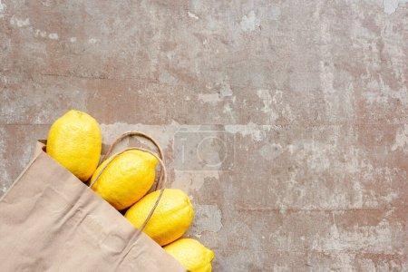 Photo pour Vue du dessus du sac en papier avec des citrons jaunes sur une surface beige altérée - image libre de droit