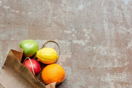 Photo for Top view of paper bag with red and green apples, lemon and orange on weathered beige surface - Royalty Free Image