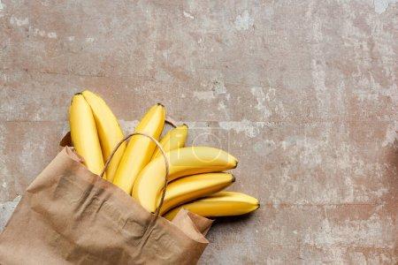 Photo pour Vue du dessus du sac en papier avec bananes sur une surface beige altérée - image libre de droit