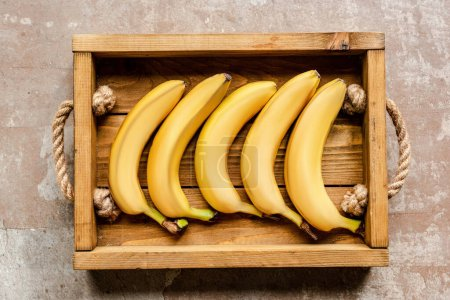 Photo for Top view of ripe bananas in wooden box on weathered surface - Royalty Free Image