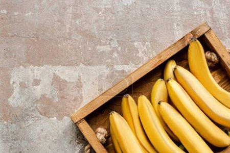 Photo pour Vue de dessus des bananes mûres dans la boîte en bois sur la surface altérée - image libre de droit