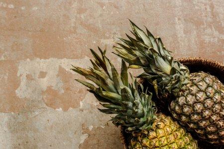 Photo pour Vue de dessus des ananas exotiques mûrs dans le panier en osier sur la surface altérée - image libre de droit