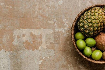 Photo pour Vue de dessus des fruits exotiques mûrs dans le panier en osier sur la surface altérée - image libre de droit