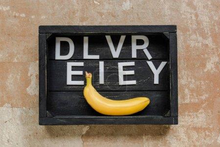 Photo pour Vue du dessus de la livraison de mot près de banane dans la boîte noire en bois sur la surface altérée - image libre de droit
