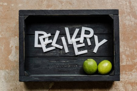 top view of word delivery near limes in wooden black box on weathered surface