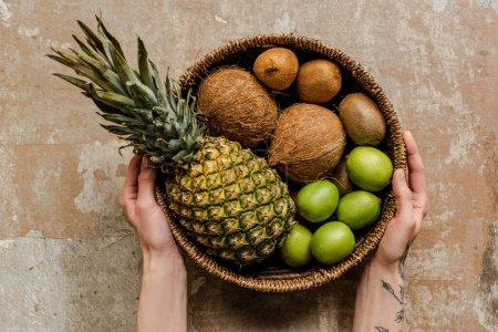 Photo pour Vue recadrée de la femme tenant des fruits exotiques mûrs dans un panier en osier sur une surface altérée - image libre de droit
