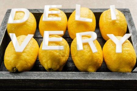 Photo pour Livraison de mots sur les citrons dans une boîte noire en bois sur une surface altérée - image libre de droit