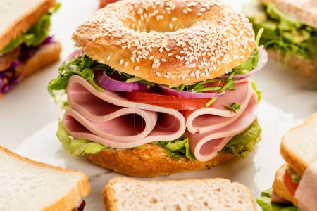 fresh delicious bagel with sausage and vegetables near sandwiches