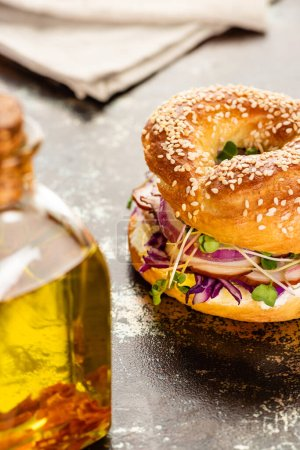 selective focus of oil and fresh delicious bagel with meat, red onion, cream cheese and sprouts on textured surface