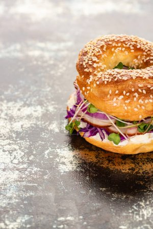 fresh delicious bagel with meat, red onion, cream cheese and sprouts on textured surface