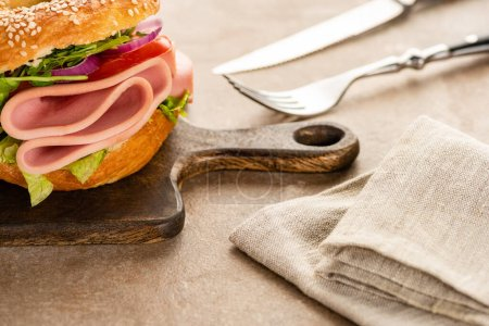 Photo for Selective focus of fresh delicious bagel with sausage on wooden cutting board near napkin and cutlery on textured surface - Royalty Free Image