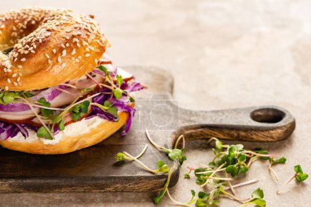 fresh delicious bagel with meat, red onion, cream cheese and sprouts on wooden cutting board