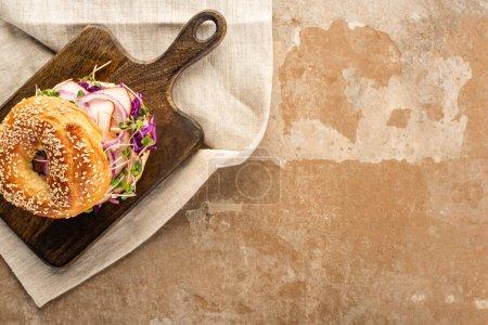 Photo pour Vue de dessus du délicieux bagel frais avec viande, oignon rouge et germes sur planche à découper en bois sur serviette sur une surface beige vieilli - image libre de droit