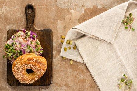 Photo pour Vue de dessus du délicieux bagel frais avec viande, oignon rouge et germes sur planche à découper en bois près de la serviette sur une surface beige vieilli - image libre de droit