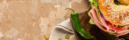 Photo pour Vue de dessus du délicieux bagel frais avec saucisse sur planche à découper en bois sur une surface beige vieilli avec jalapenos, vue panoramique - image libre de droit