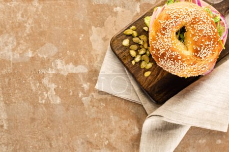 Photo for Top view of fresh delicious bagel on wooden cutting board with pumpkin seeds on aged beige surface with napkin - Royalty Free Image