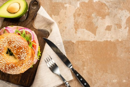 top view of fresh delicious bagel on wooden cutting board on aged beige surface with avocado, cutlery and napkin