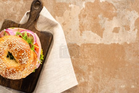 Photo for Top view of fresh delicious bagel on wooden cutting board on aged beige surface with napkin - Royalty Free Image