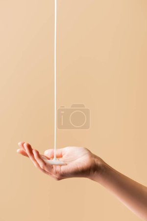 Photo for Partial view of female hand under flowing liquid soap isolated on beige - Royalty Free Image