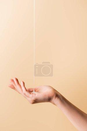 Photo pour Vue recadrée de la main féminine sous du savon liquide coulant isolé sur beige - image libre de droit