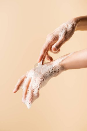 Photo for Partial view of female hands in soap foam isolated on beige - Royalty Free Image