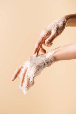 Photo pour Vue partielle des mains féminines en mousse de savon isolée sur beige - image libre de droit