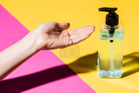 Photo for Cropped view of female hand near bottle with liquid antiseptic on pink and yellow - Royalty Free Image