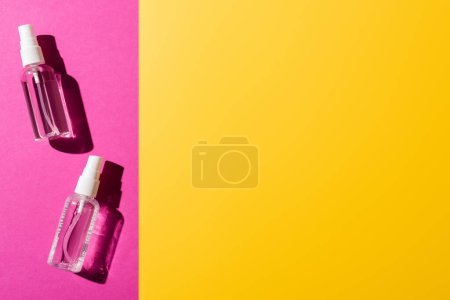 Photo for Top view of transparent spray bottles with sanitizer on pink and yellow - Royalty Free Image