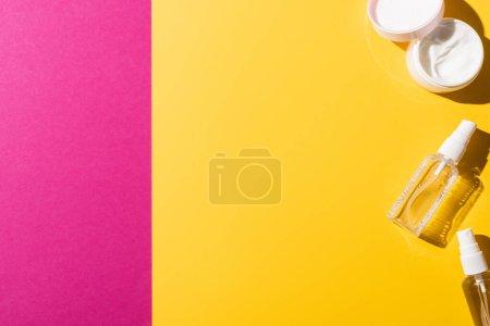 Photo pour Vue du dessus des désinfectants près de la crème pour les mains sur rose et jaune - image libre de droit