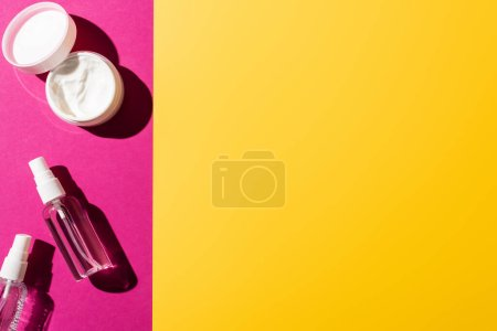 top view of spray bottles with antiseptic near hand cream on pink and yellow