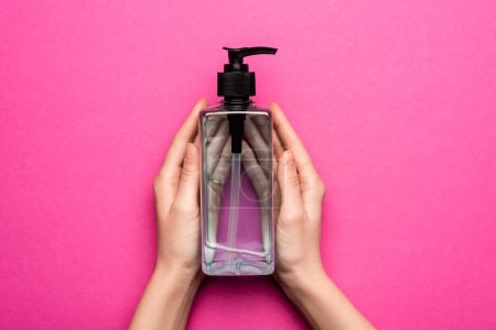 Photo for Cropped view of female hands with bottle of sanitizer on pink - Royalty Free Image