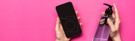 Photo for Partial view of woman holding sanitizer and smartphone with blank screen on pink, panoramic shot - Royalty Free Image