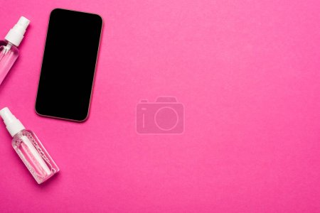 top view of spray bottles with disinfectants near smartphone with blank screen on pink