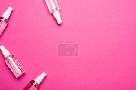 Photo pour Vue du dessus des vaporisateurs transparents avec désinfectant liquide sur rose - image libre de droit