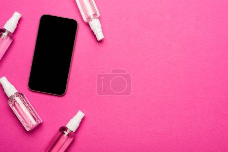 Photo pour Vue du dessus des vaporisateurs transparents avec désinfectant près du smartphone avec écran blanc sur rose - image libre de droit