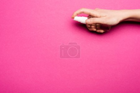 cropped view of woman spraying hand sanitizer on pink