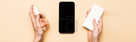 Photo for Horizontal image of female hands with sanitizer and paper napkins near smartphone with blank screen on beige - Royalty Free Image